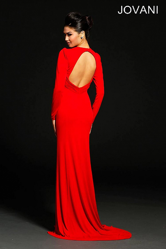Red floor length gown with long sleeves and a thigh high slit.